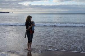 Dittte med Beco bæresele på strand in New Zealand